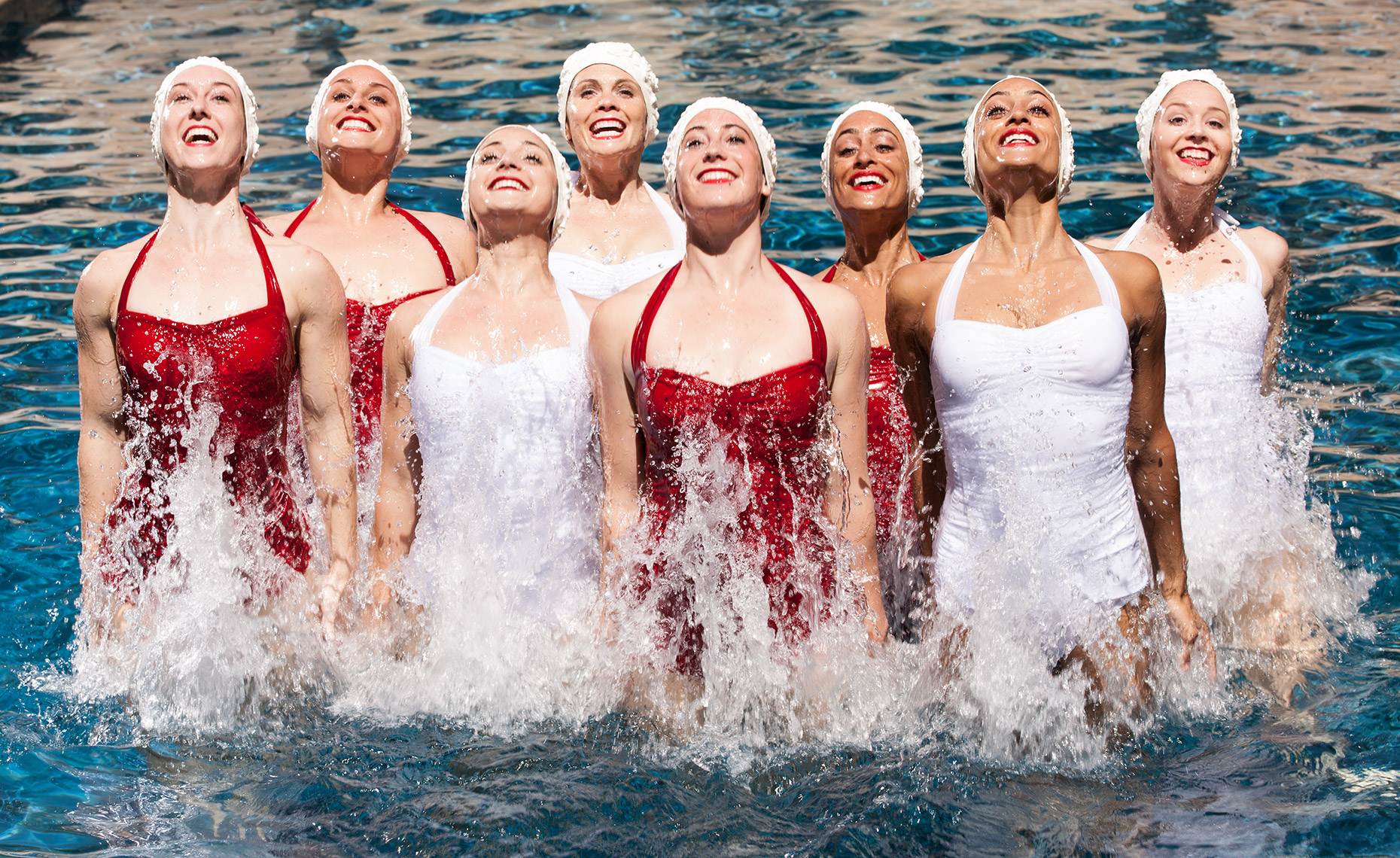 Eight women wearing white and red swimsuits jumping out of the water in unison. Advertising