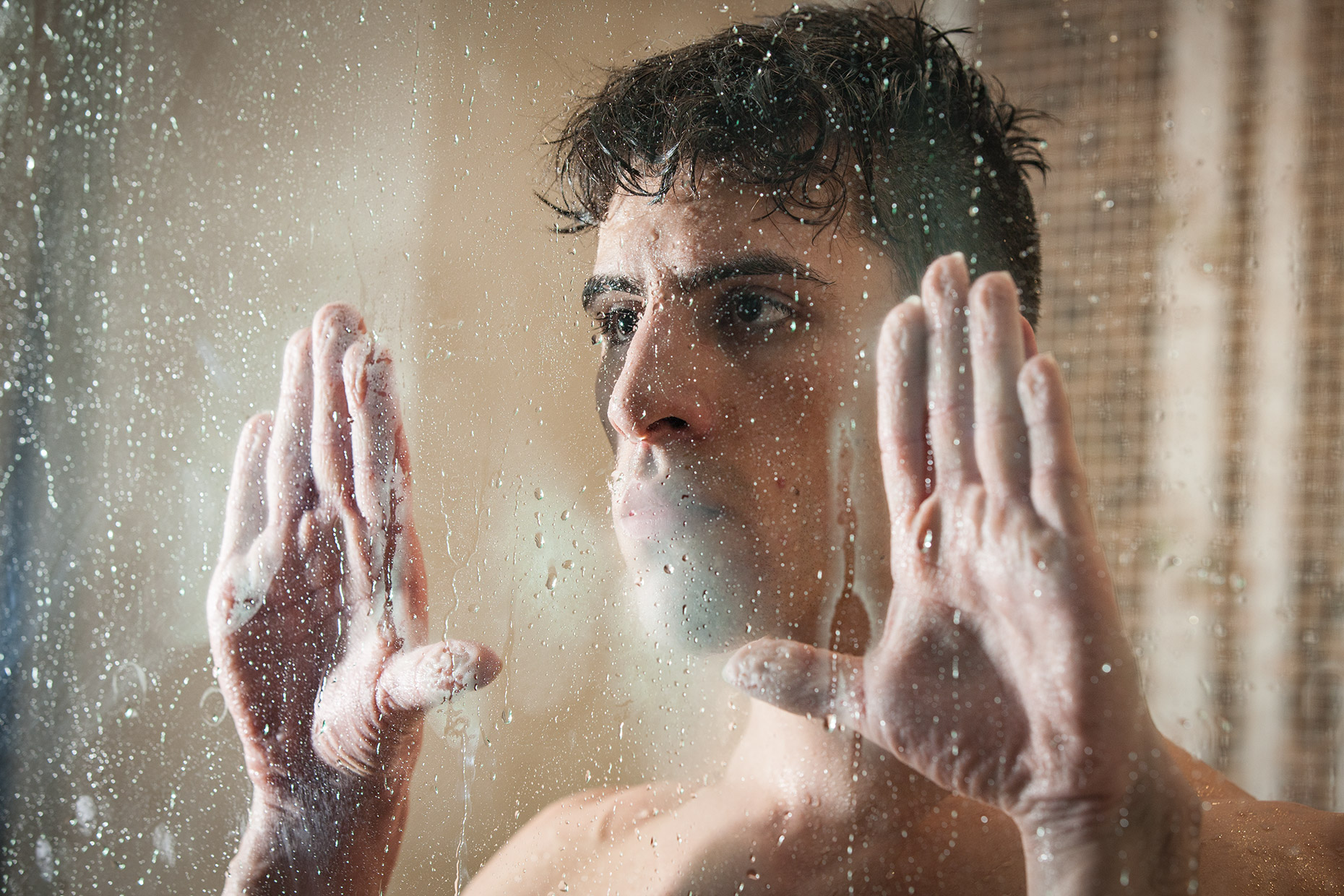 A man looking through a foggy glass window. Fine art editorial portrait.
