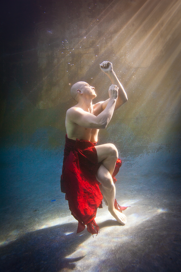 Underwater yoga wearing long red skirt.