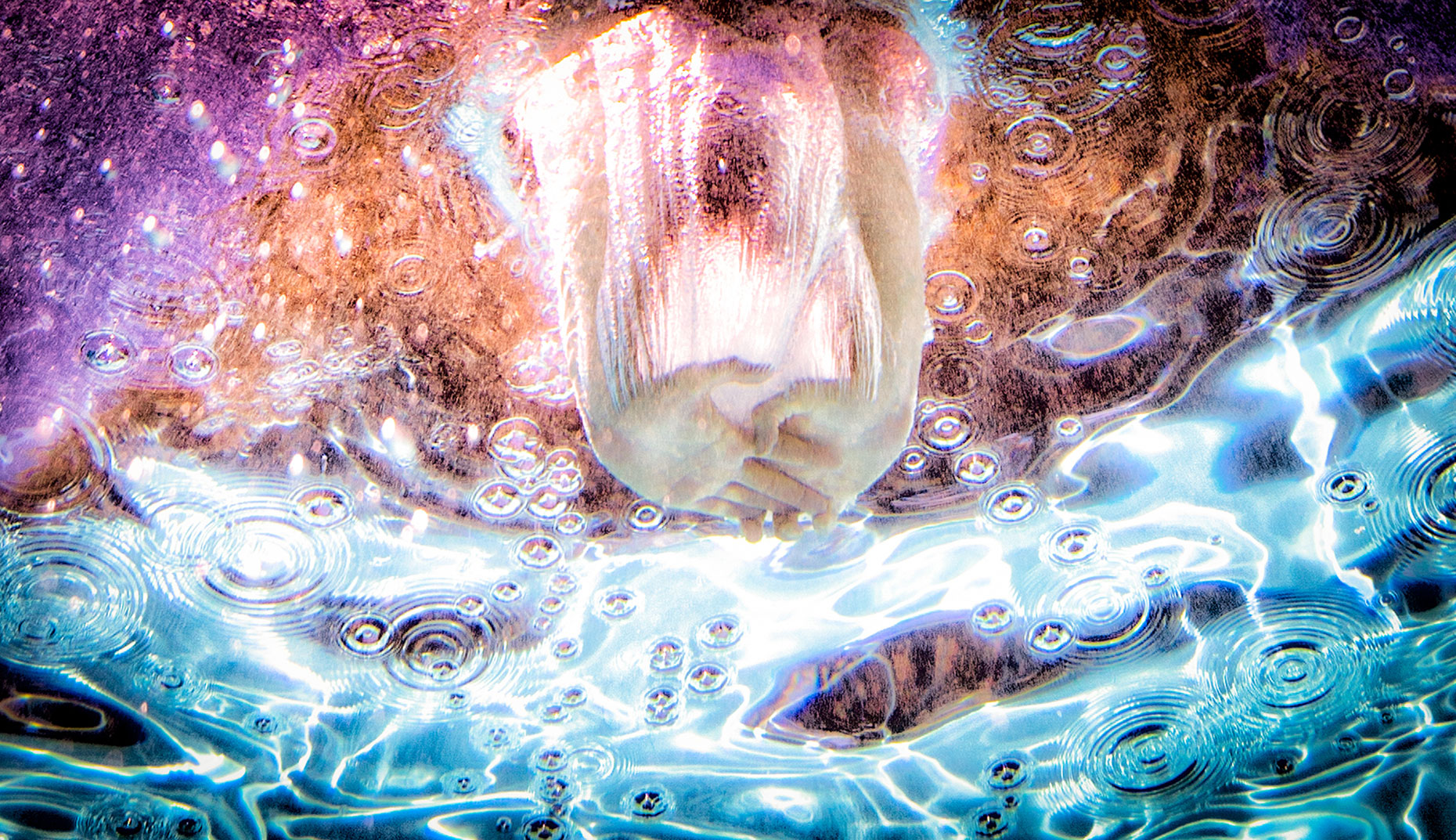 Springboard divers hands breaking the water underwater view. High speed bubbles and water droplets  advertising , commercial