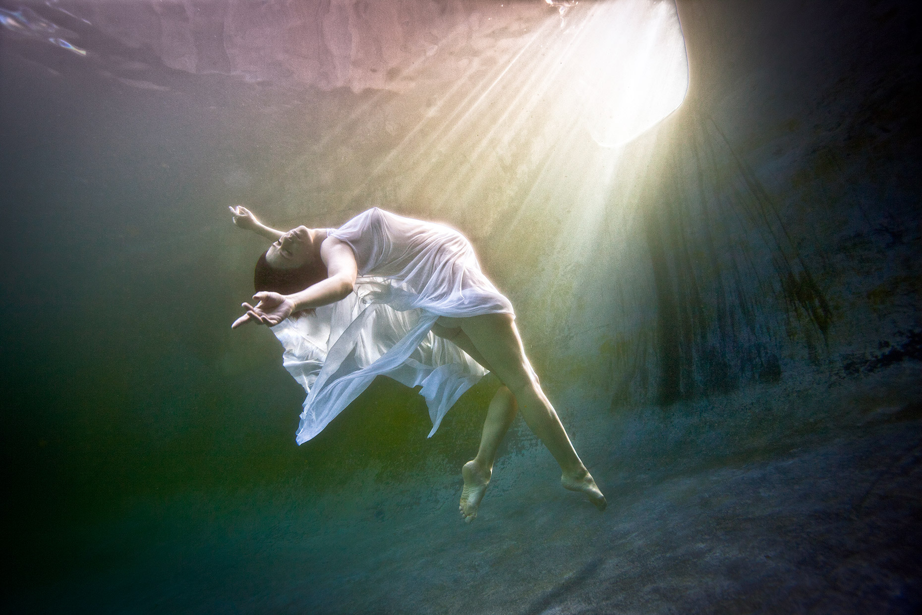 underwater floating pregnant woman in an enchanted pool
