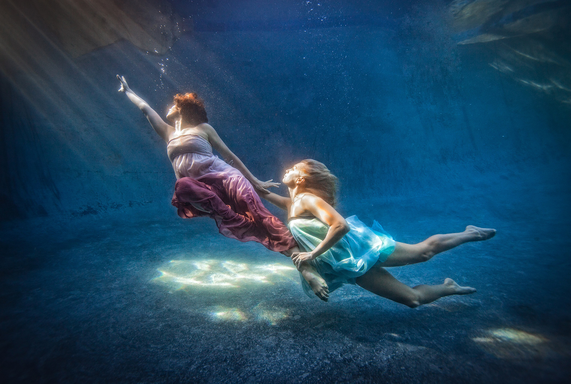 Under water chase two women chasing each other wearing dresses