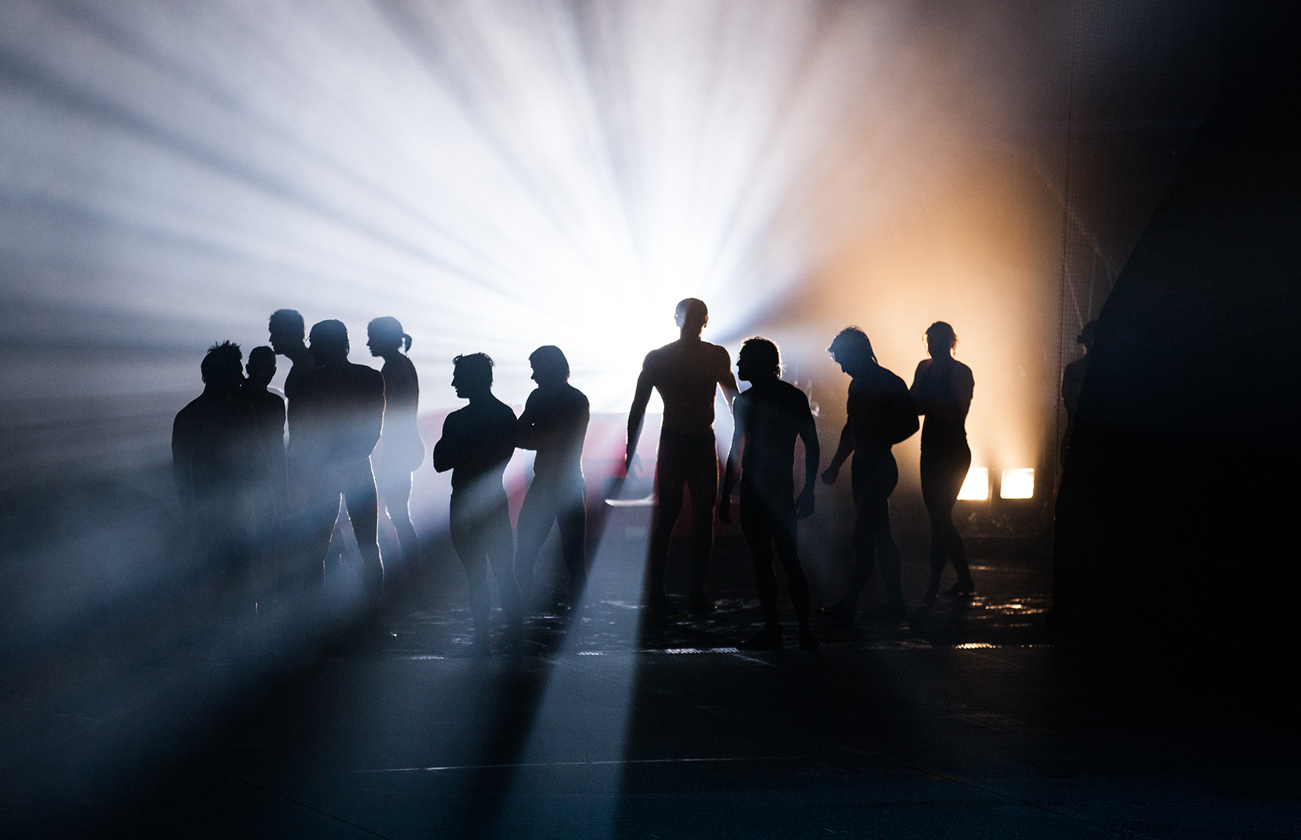 A group of people coming out of a fog surrounded by multicolor light. Advertising photograph of The House Of Dancing Water show at the City Center Hotel and Casino in Macau China.