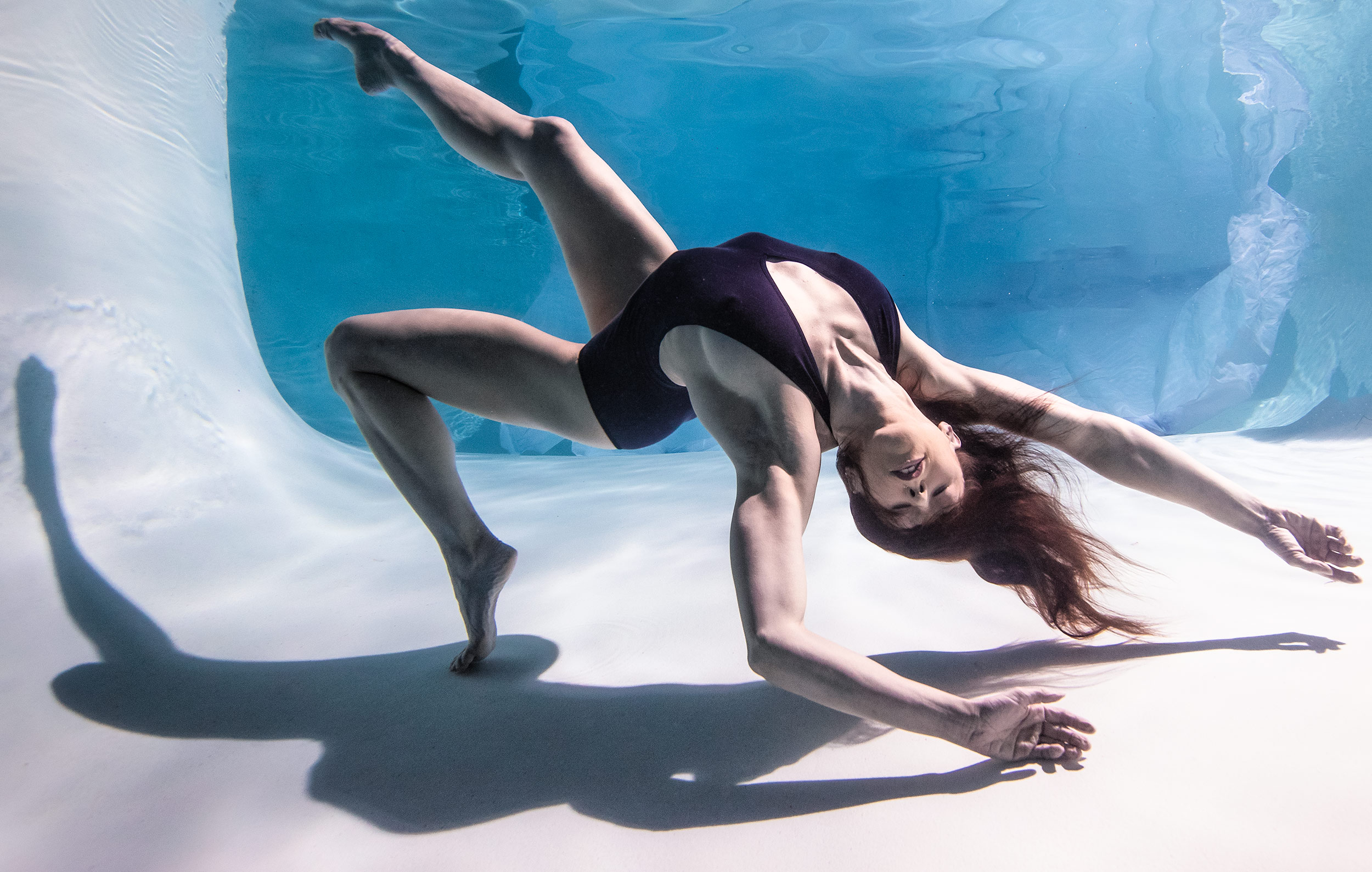 Underwater dancer performing a contorted move with her hair flowing. Cirque du Soleil performer.