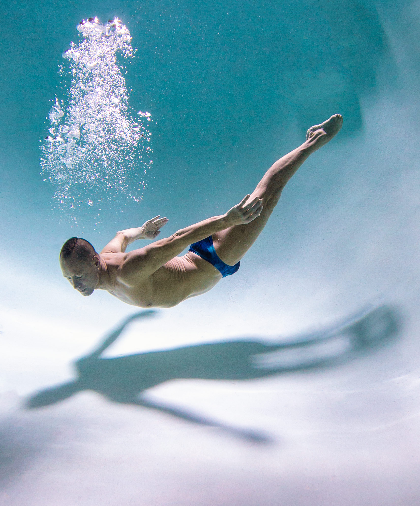 World champion synchronized swimmer floating towards the bottom of the pool. Underwater photography advertising . Bill May