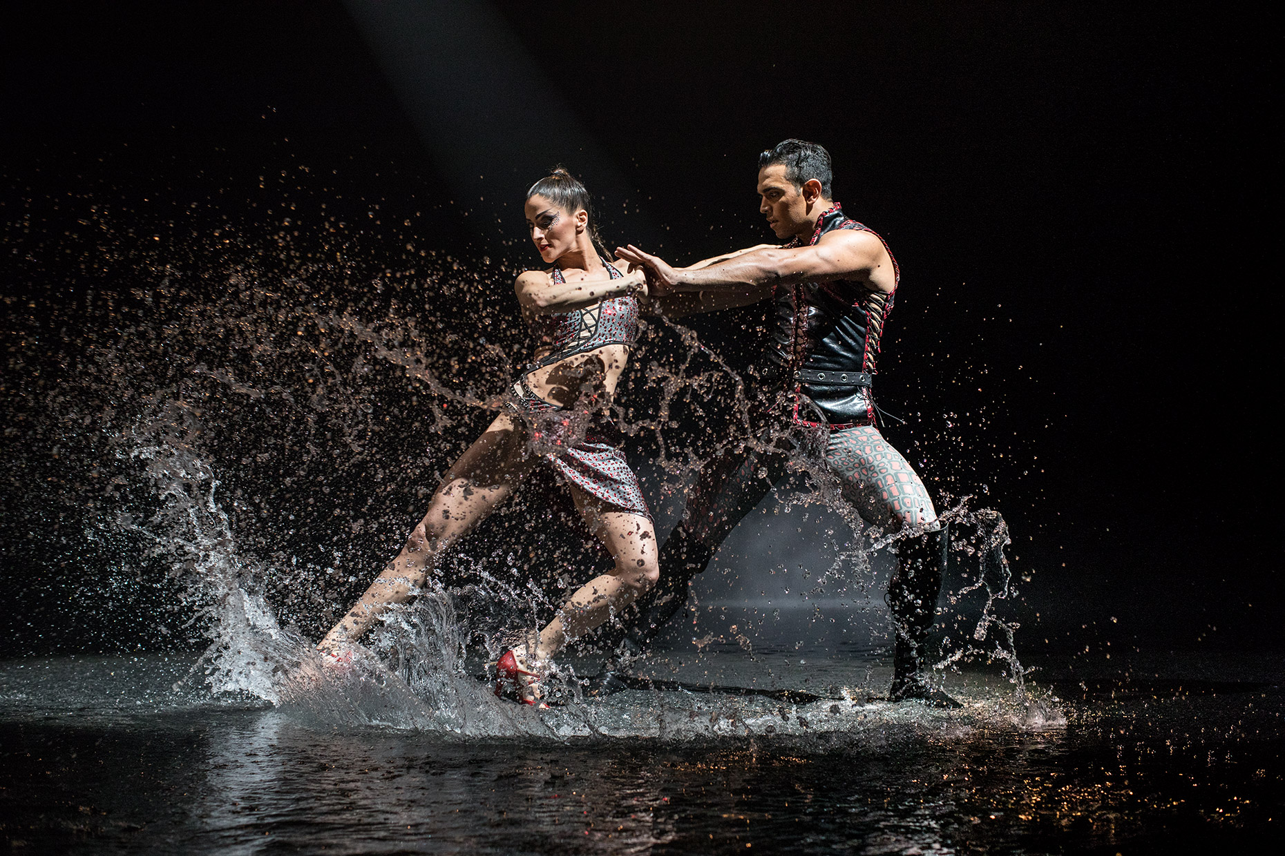 Two ball room dancers in a tango splashing water. Advertising photo for Le RÊVE the show at Wynn Las Vegas.
