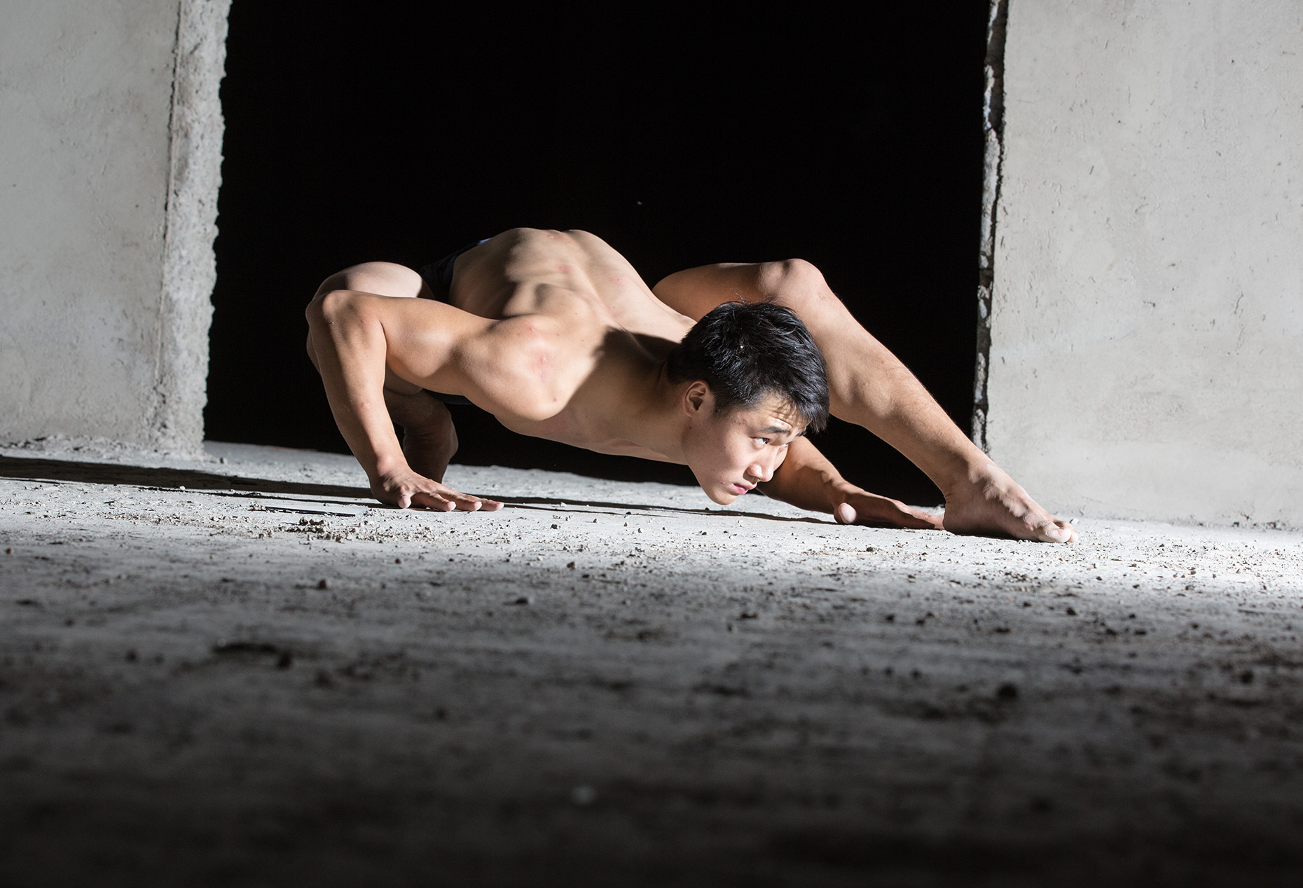 male contortionist performer crawling on the floor of an abandoned concrete structure. strange position. Cirque du Soleil. Fine art, editorial , portrait.