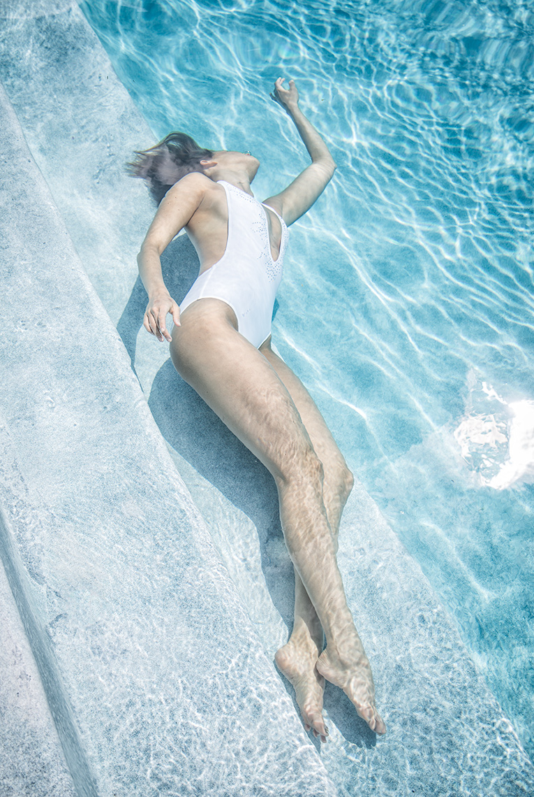 Underwater surrender in white swimsuit